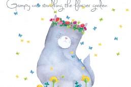 ふてネコが花畑に佇む